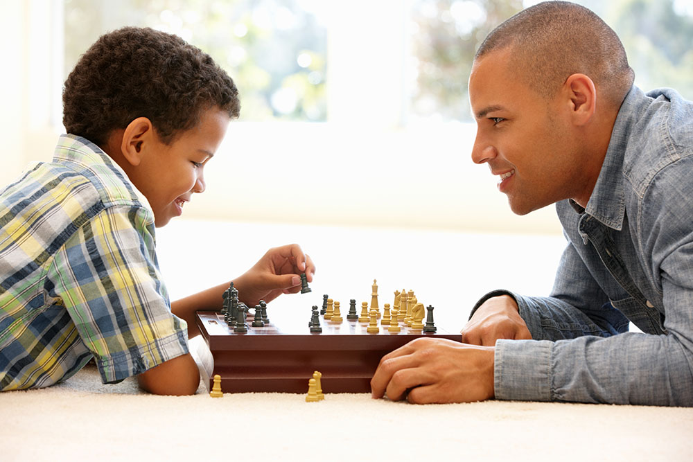 Father playing chess with son on clean carpet by triple j carpet cleaning company